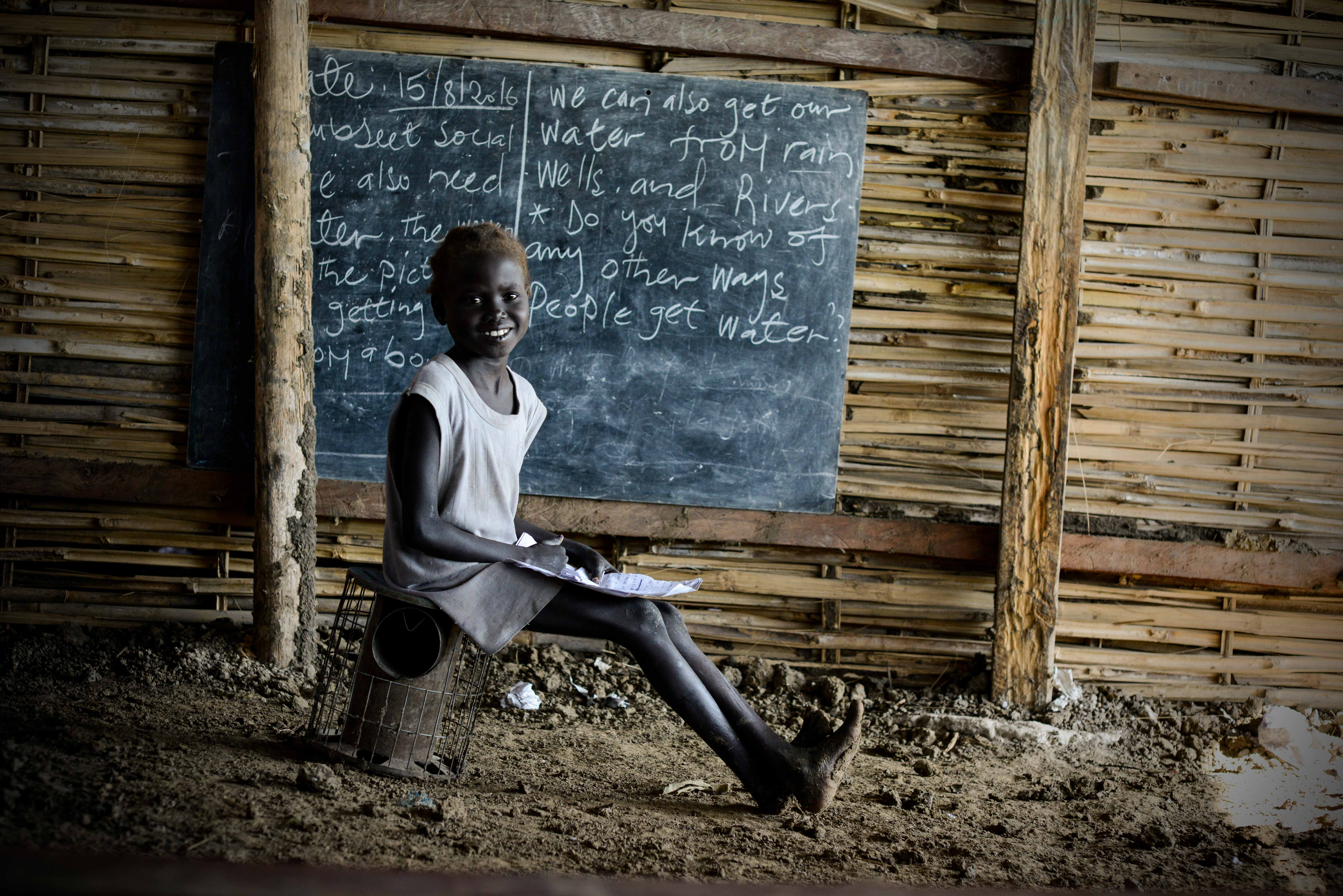 Little girl sits on a cookstove, with a notebook on her lap and a blackboard in the background