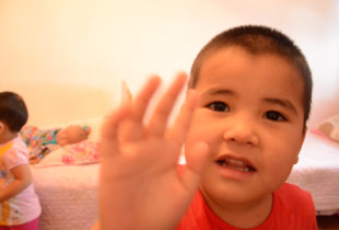 Closeup of toddler's head and hand, waving at the camera