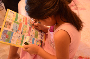 LIttle girl seen from above as she works on a coloring book