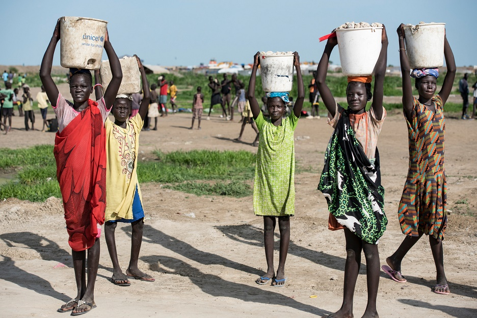 A group of girls carrying water containers on their heads.