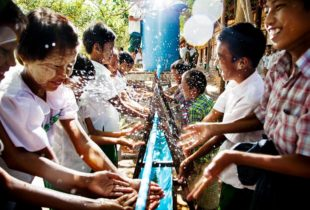 Children at a long trough of water wash their hands.