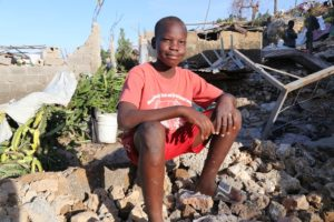 A boy sits on a pile of rubble.