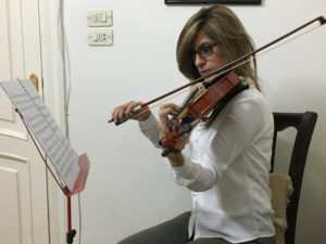 Woman sitting, playing a violin as she reads from sheet music