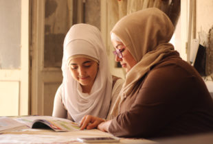 Young woman and girl sitting together over a schoolbook
