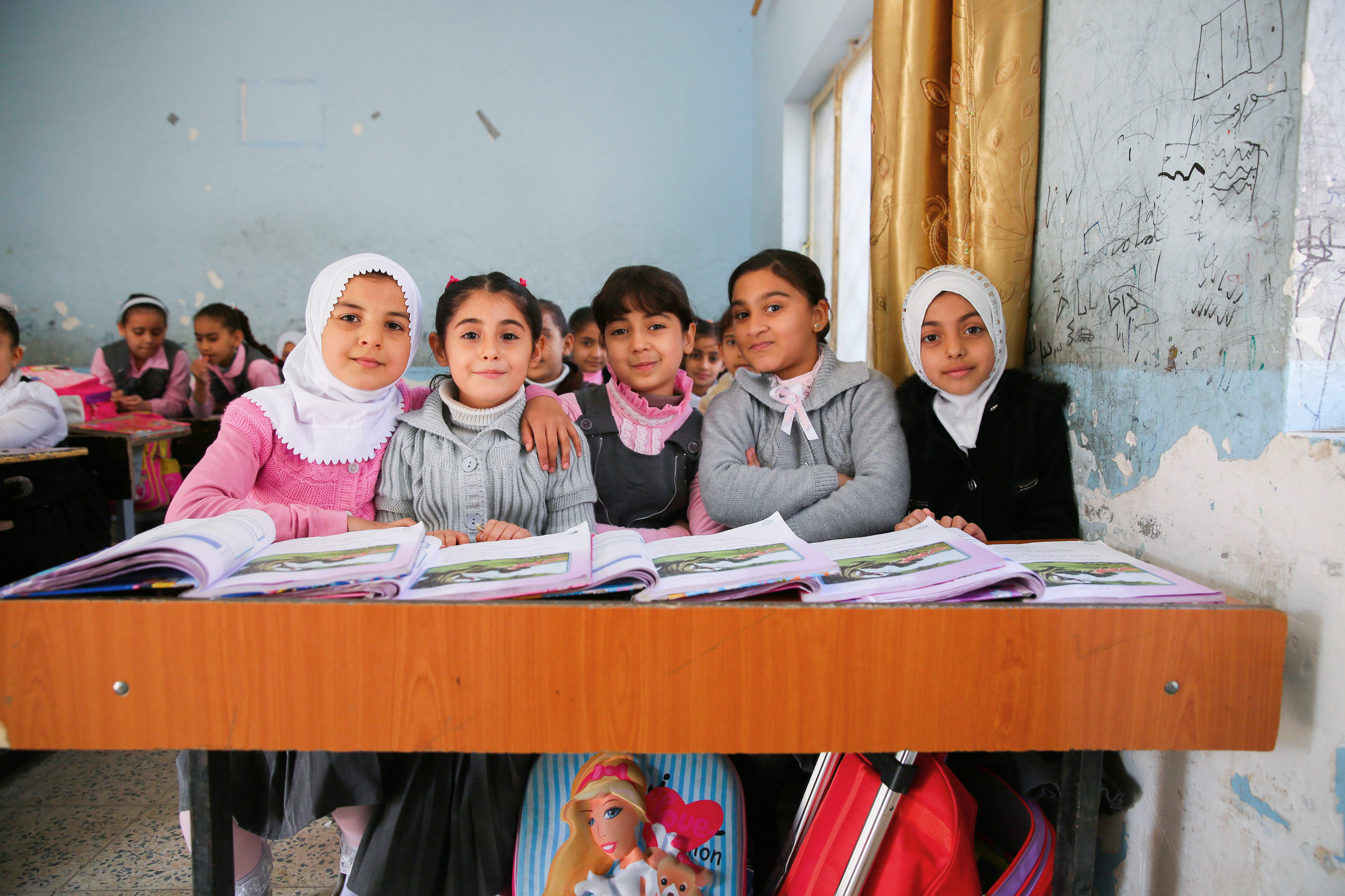 Five little girls sit at their school desk, smiling, their books open on the desk
