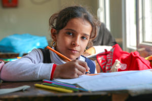 Girl looks up from her notebook in class, orange pencil poised in mid-air
