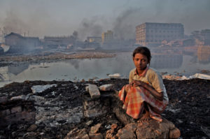 Girl squats on a rock in front of a stagnant body of water, with smoke and buildings in the background