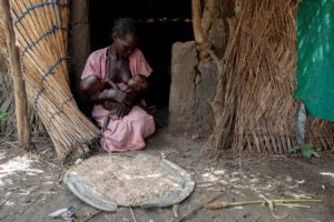 Woman sits at door of straw and mud hut breastfeeding two babies. A tray of grass seed lies before her on the ground.