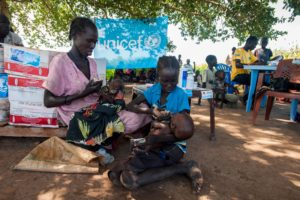 Woman and girl sit on the ground, each holding a baby and feeding him peanut butter paste from a sachet.