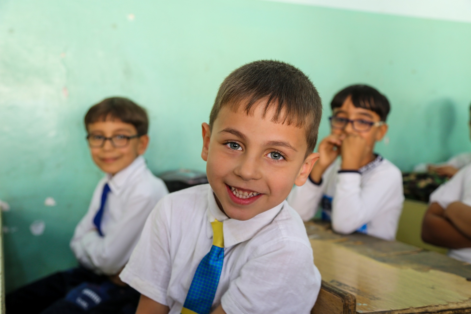 A boy in a shirt and tie in his classroom.