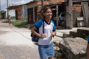 A young woman in a backpack walks along the street.