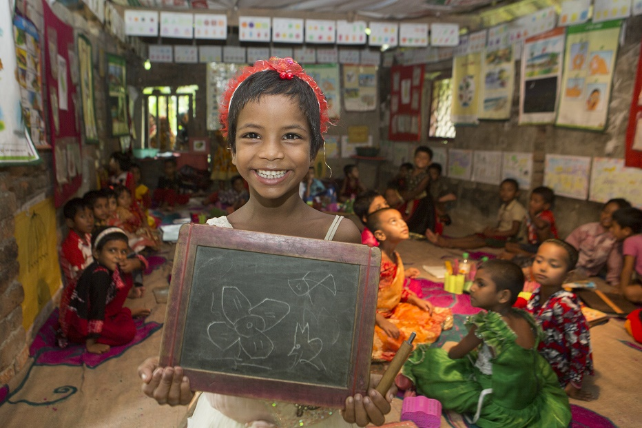 A girl, smiling, holds a small chalkboard with her drawing on it.
