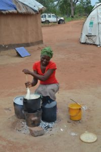 Woman smiles as she stirs food in a pot over a clay stove