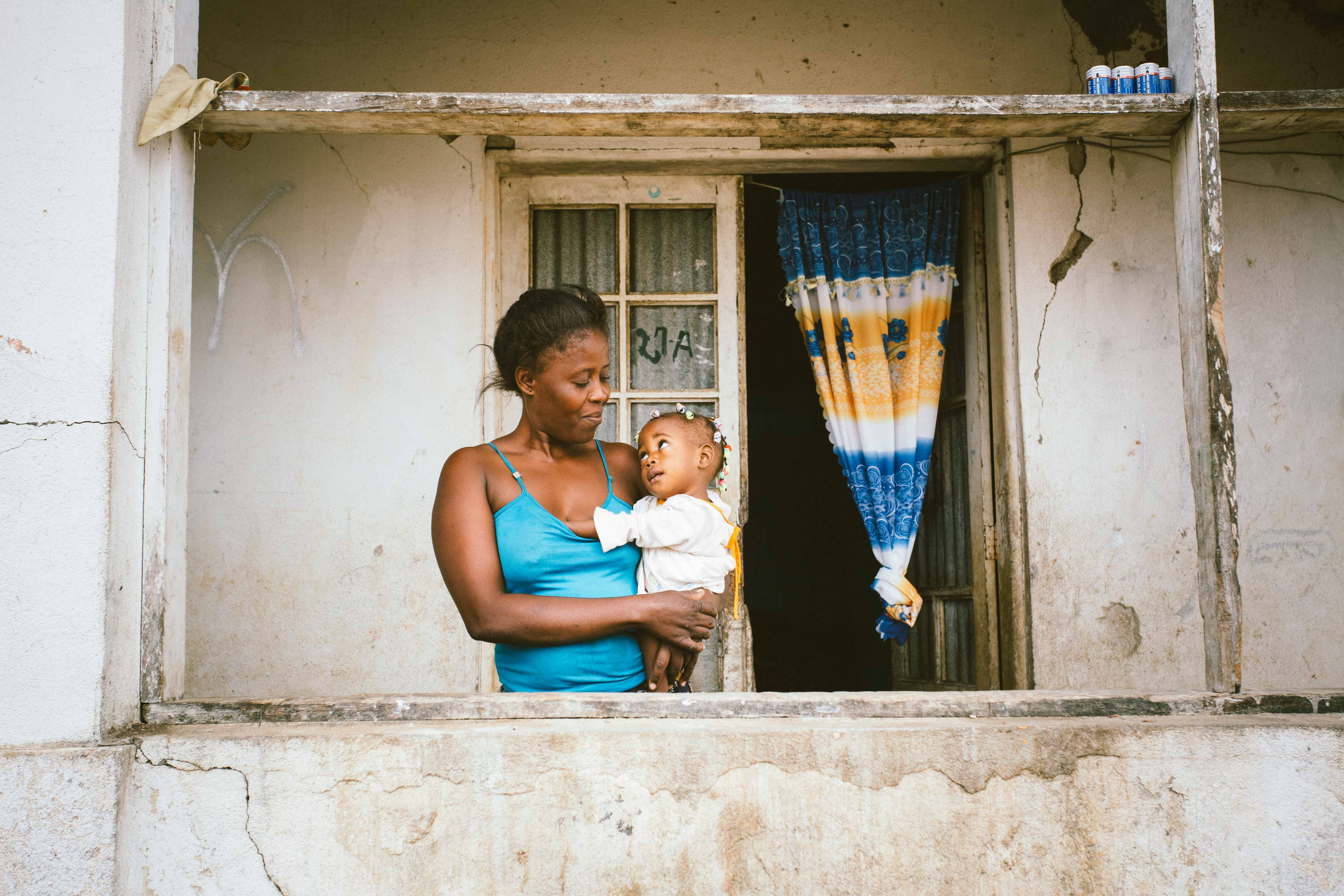 Woman standing on balcony holding a baby; they look at each other