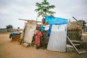 Mother holding baby and small child stand in front of a shack