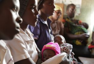 Women listening to teacching while holding their babies