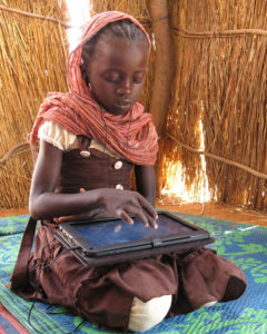 Little girl looks and points at her tablet screen
