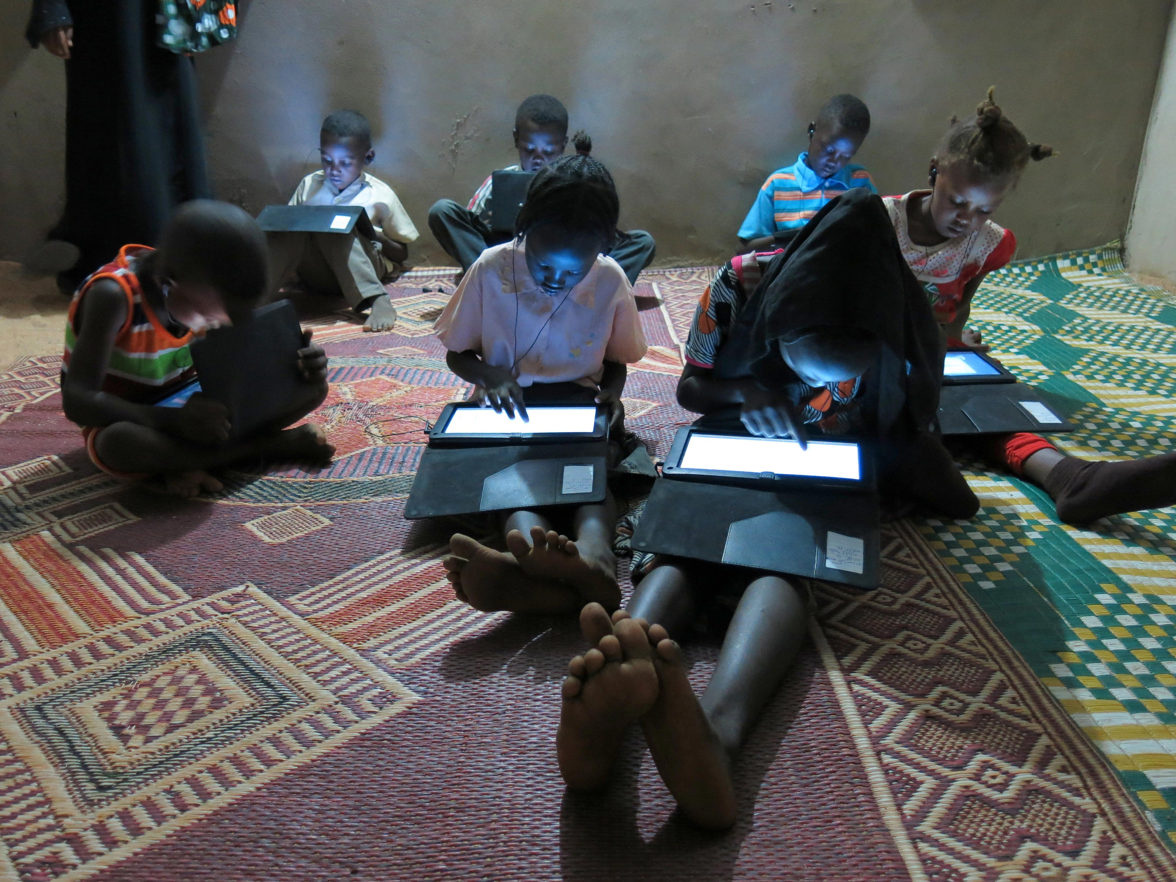 Children sit on a patterned rug, bent over brightly lit tablet screens