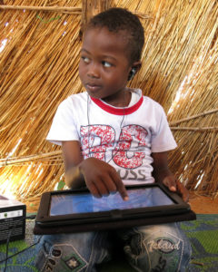 Child with earbuds, pointing to something on a tablet screen while kneeling on a blue and green rug in a thatched building