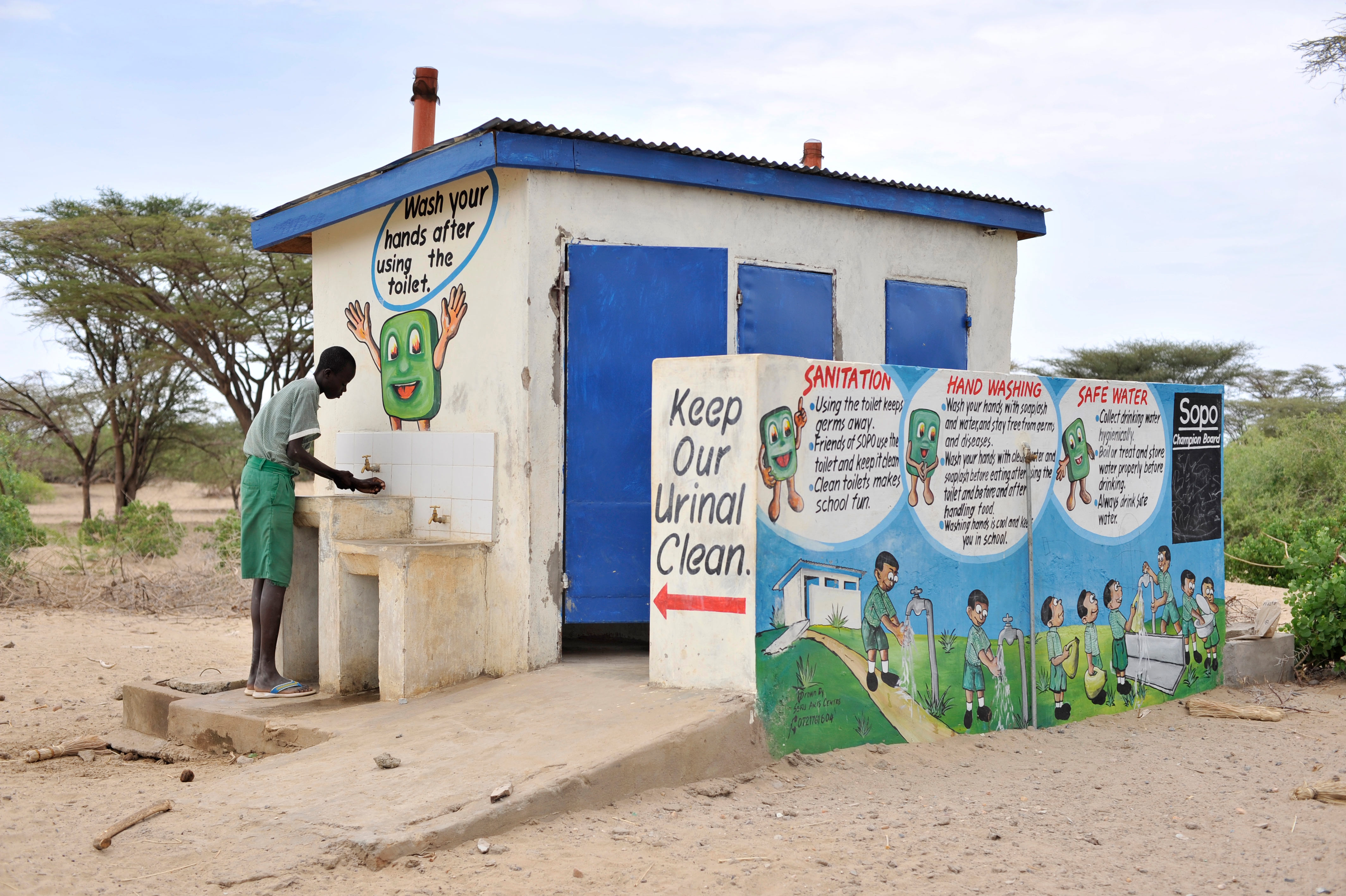 Boy washes his hands at a sink outside a public toilet building painting with informational messages on sanitation and handwashing