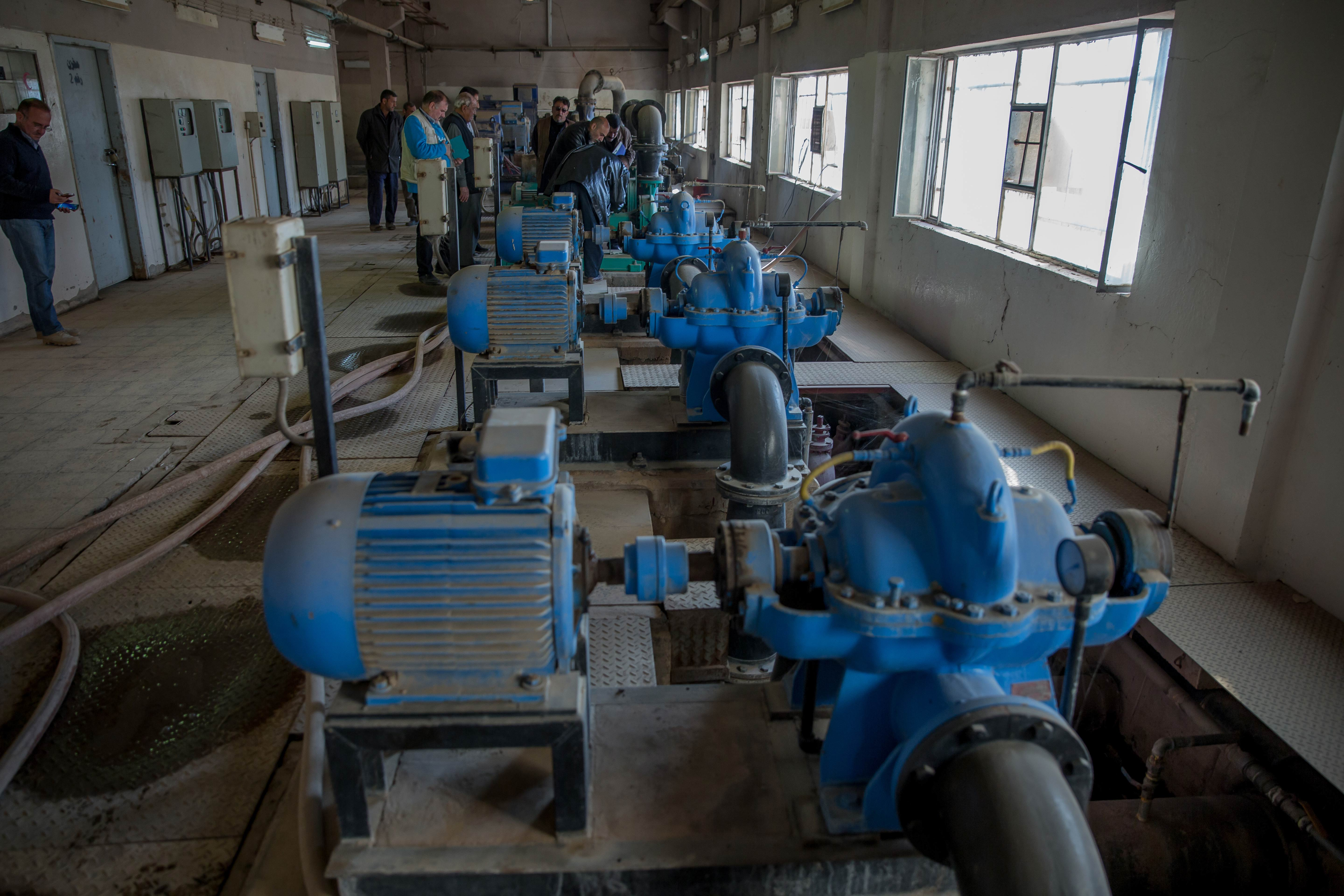 People stand around machinery in a room