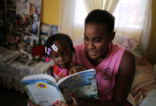 Little girl points to something in a book a young woman is reading to her