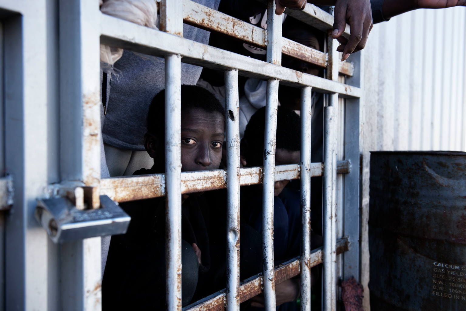 A boy looks out from behind the bars of a cell at a detention centre.