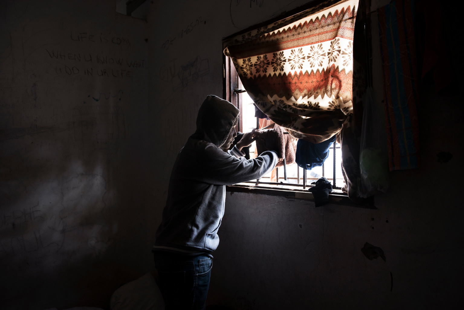 A migrant looks through the window of one of the detention centres.