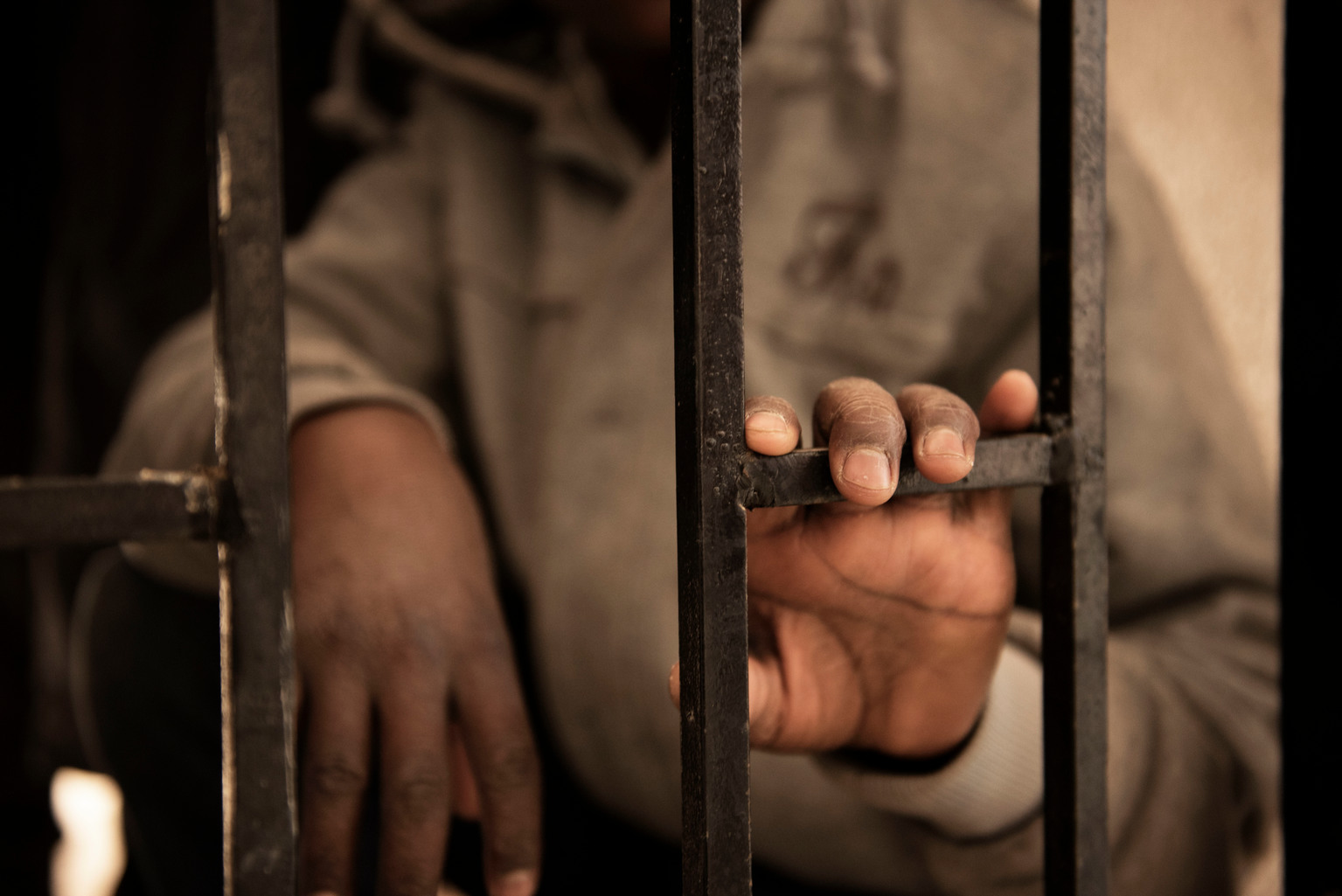 Fourteen-year-old Issaa, a migrant from Niger, rests his hand on a gate inside one of the detention centres.