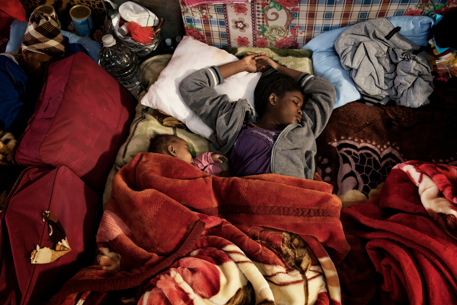 A woman and child sleep on old mattresses laid on the floor at one of the detention centres.