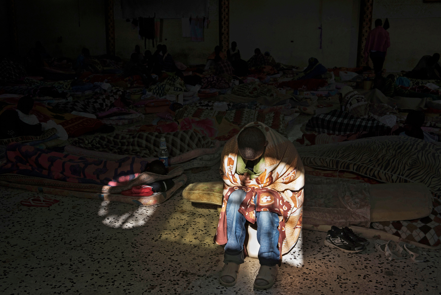 A migrant sits in a patch of light entering through one of only two windows as he tries to warm himself up at the Al Saladdin detention centre, Tripoli, Libya.