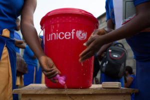 One girl's hand opens a tap on a red plastic bucket with the UNICEF logo, while another girl's hands wash each other.