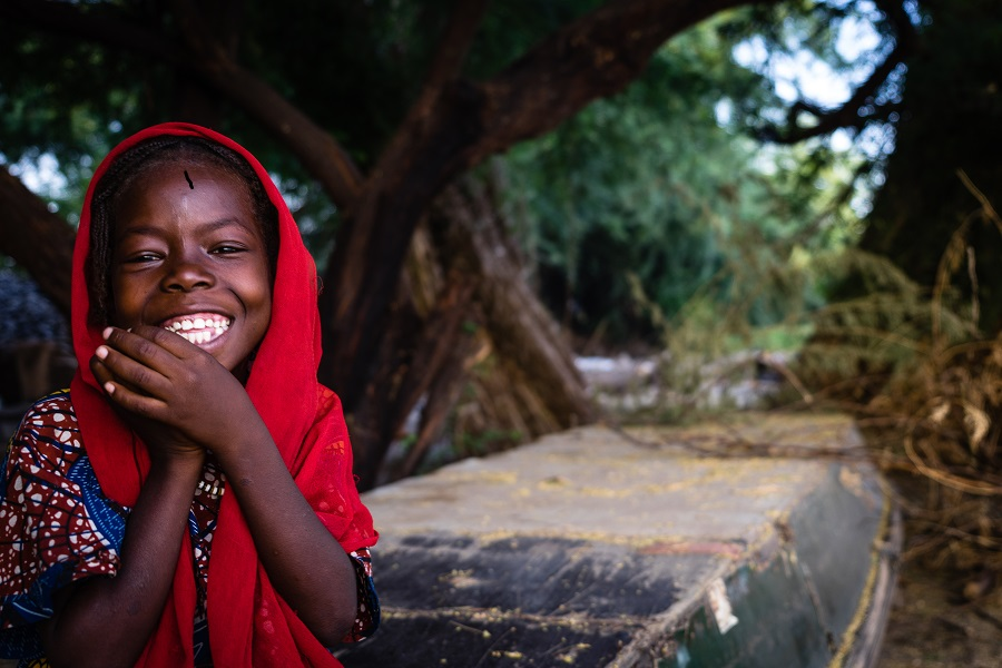 A girl in red head covering smiles at camera..