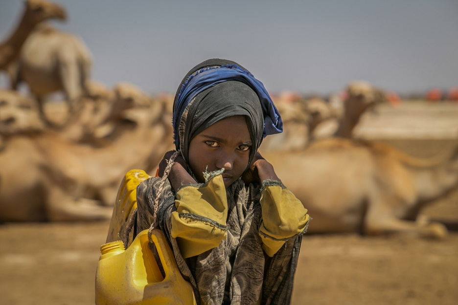 A girl walks along a dusty rode carrying water.