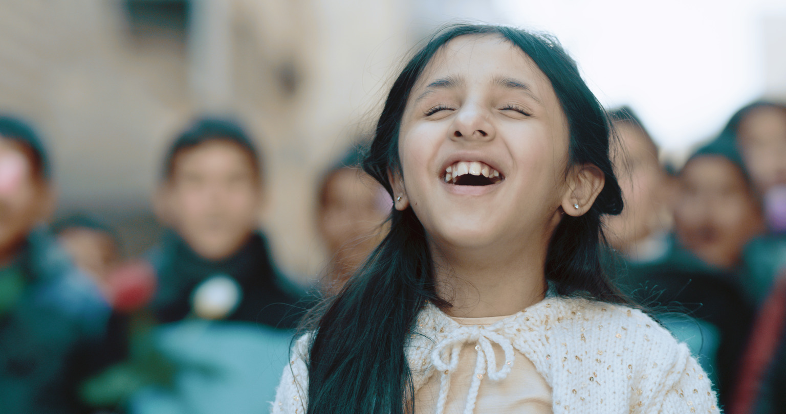 A close up of a girl singing with her eyes closed.