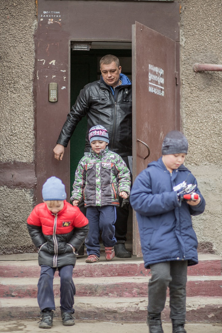 A man and three children exit an apartment building together.
