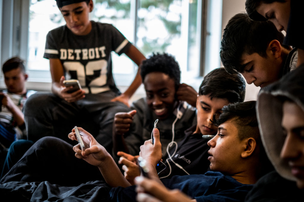 Sajad and Zein play Clash of Clans with other refugees.