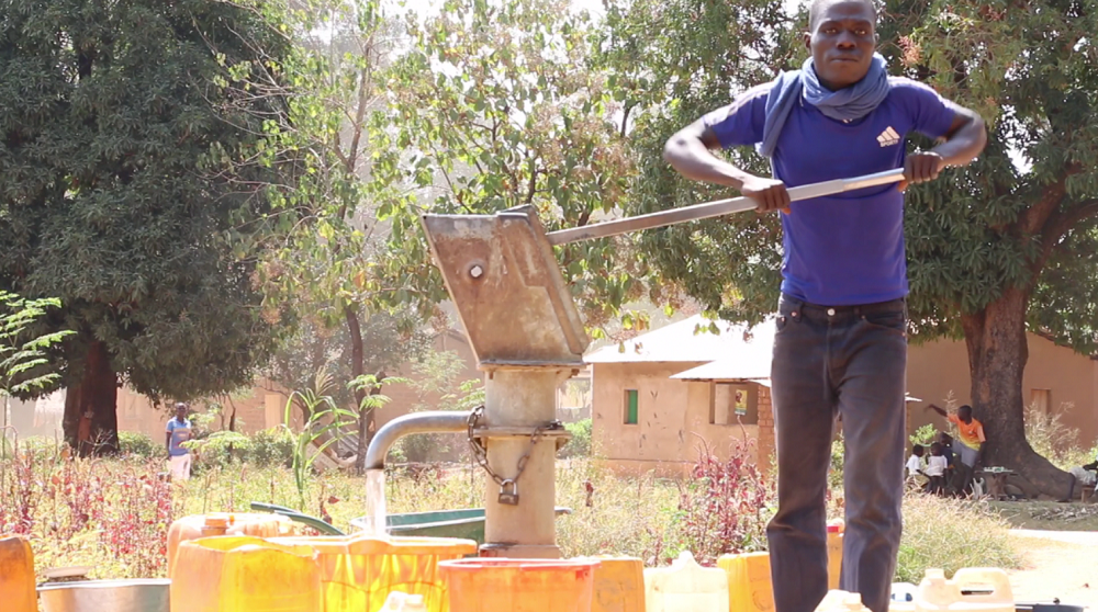 A young man in a purple tee shirt stands as he pumps water