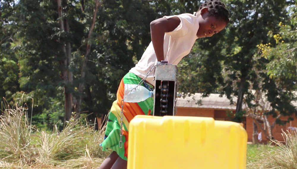 A woman in a white shirt pumps water by hand.