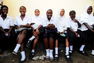 A group of girls in school uniforms sit on a bench.