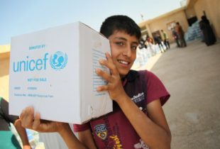 A boy holding a box with a UNICEF label on it