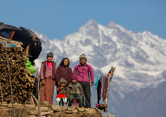 A family stands in colorful cothing on a mountain together.
