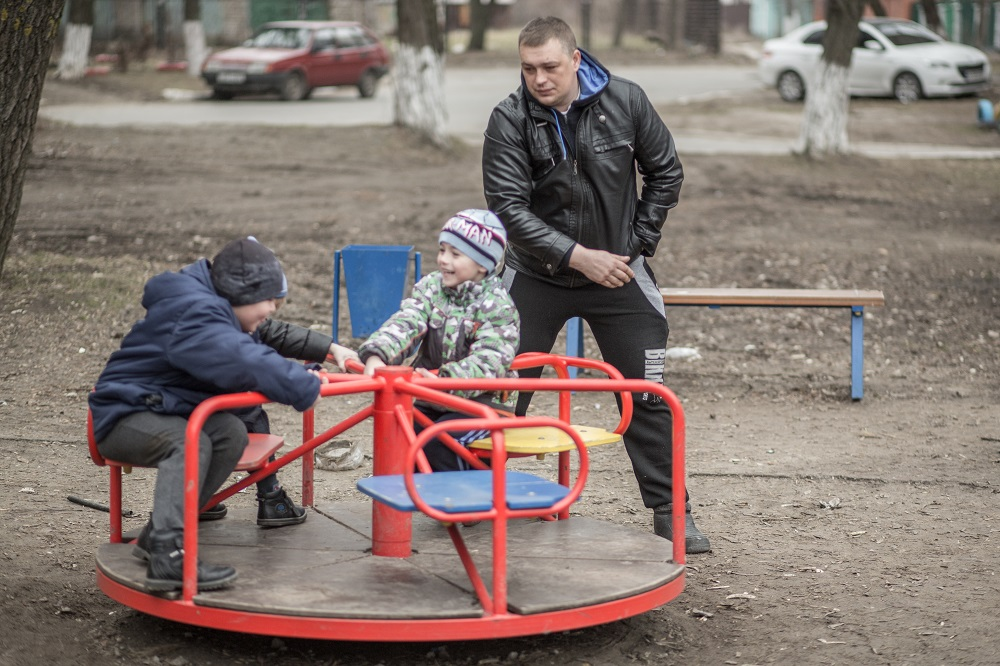 A father watches as his sons play on a merry go round