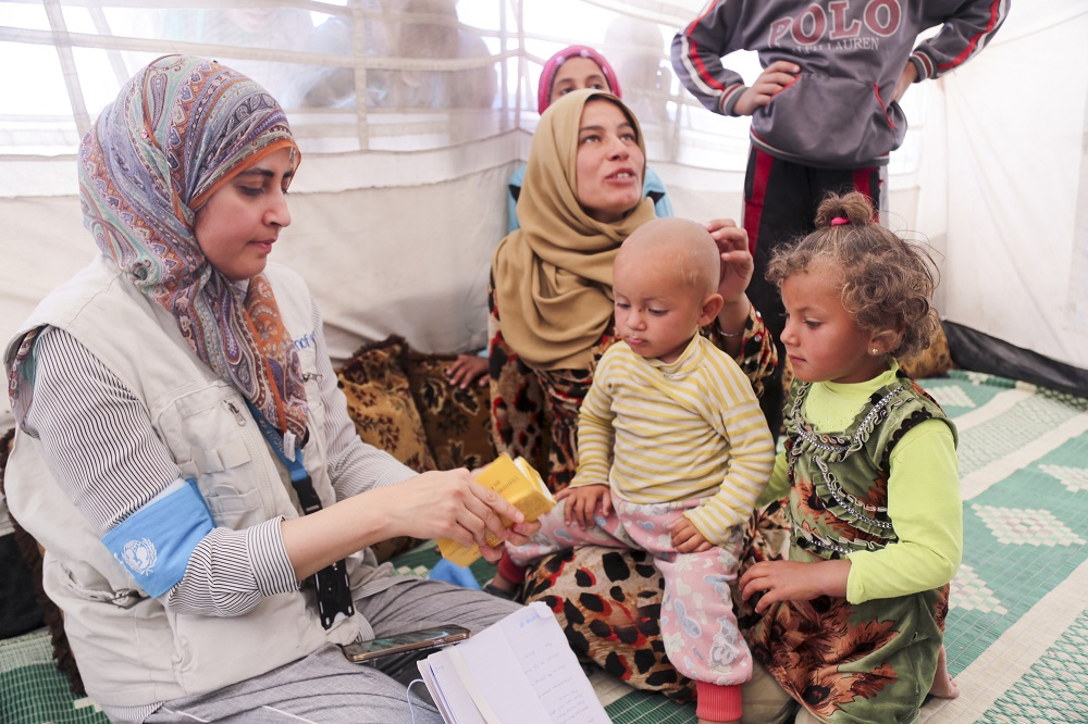 A woman in a headscarf screens two young children for malnutrition while their female caregiver looks on.