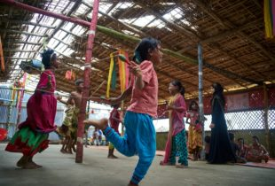 A group of colorfully dressed girls and boys jump rope.