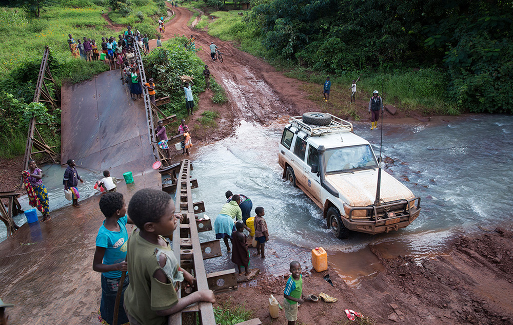 Children stand on a destroyed bridge watching a white four wheel drive ford a shallow river