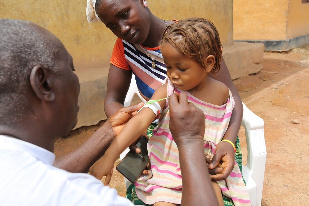 A man in a white coat measures the upper arm of a young girl as a woman looks on.