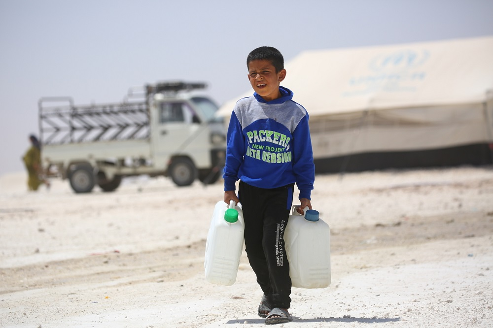 A boy in a blue shirt carries two water containers across dusty ground.