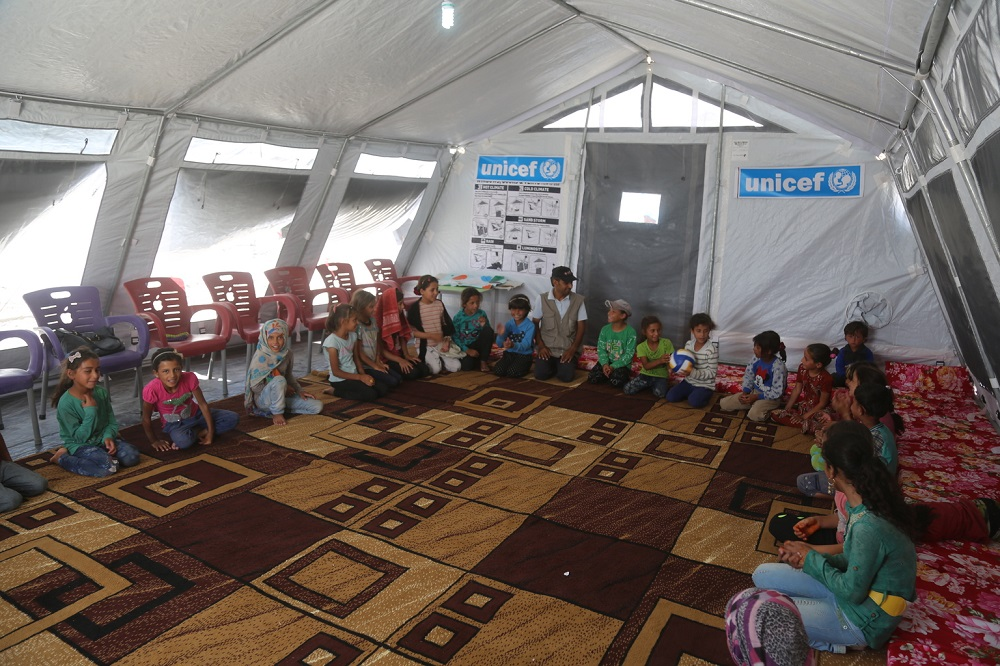 Children sit in a circle inside a tent with UNICEF signs in the background.