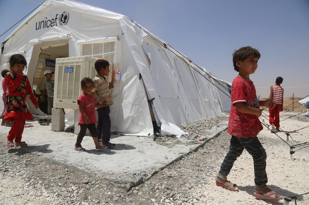Three children walk past a tent with a airconditioner attached.